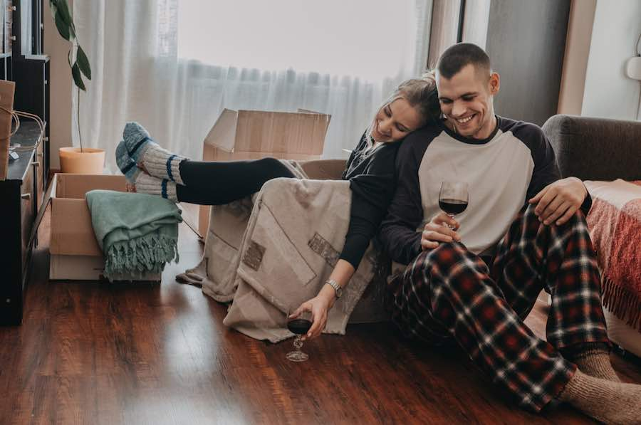 male and female couple sitting on the floor surrounded by moving boxes